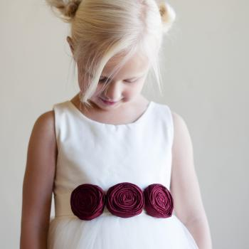 A young flower girl at a wedding wearing an ivory flower girl dress with tulle skirt and three red roses on the belt.