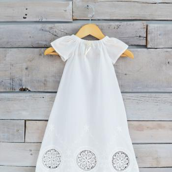 A pretty antique white christening gown with a lace hem and an elasticated neckline with a pretyy organza bow and ribbon.