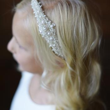 A young flower girl wearing a high quality beaded headband for flower girls and first communion hair styles in ivory.