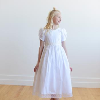 A girl wearing a bespoke white cotton first communion dress with puff sleeves and a lace trim at the waist and the hem.