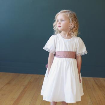 A toddler wearing a cotton flower girl dress with lace at the neck and sleeve. The dress is available in ivory or white and comes with a pure silk sash.
