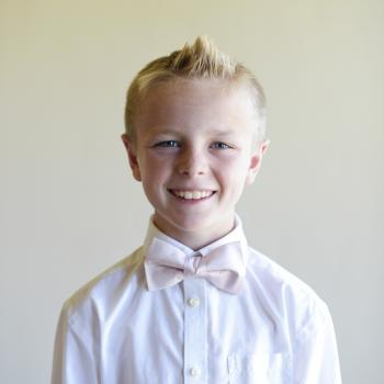 A pageboy at a wedding wearing a blush pink silk bow tie that is pre-tied