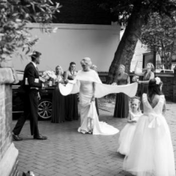 A bride getting in to her wedding car with two bridesmaids and two flower girl swearing a ruffle silk flower girl dress with a full tulle skirt and a big bow. These flower girl dresses are handmade to measure in London, UK.
