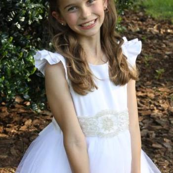 An 8 year old girl wearing a whit silk flower girl dress and first communion dress with diamante on the sash.