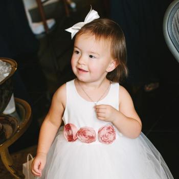 A little, toddler flower girl wearing an ivory flower girl dress with a tulle skirt and peach roses.