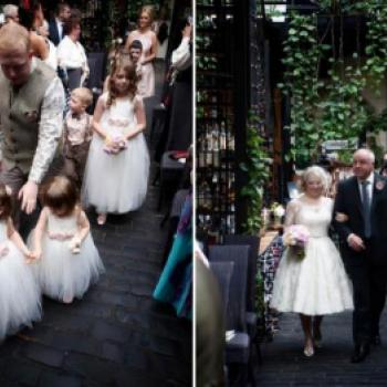 A bride and a group of flower girls at a wedding in Scotland. The bride has a 1950s style dress and the flower girls are wearing a cotton and tue dress with blush pink flowers.