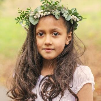 A flower girl with a green wreath on her head and a short sleeved, ivory flower girl dress.