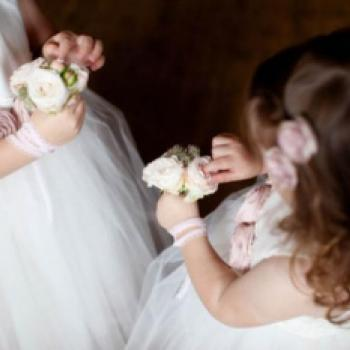 Two flower girls holding pink rose bouquets. The flower girl dresses are in ivory cotton and have blush pink flowers on the sash.