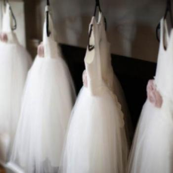 Four flower girl dresses in ivory cotton with a tulle skirt and blush pink flowers.