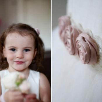 A photo of a flower girl wearing a cotton ivory and pink flower girl dress or junior bridesmaid dress with pretty pink silk roses.