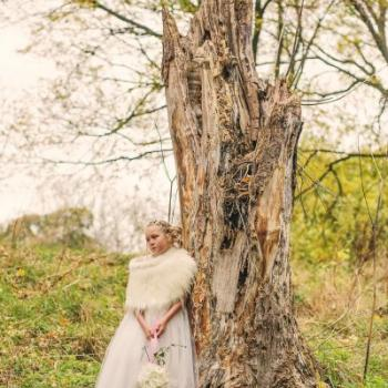 A young flower girl standing under a tree wearing an ivory tulle flower girl dress and a feathered cape shawl.