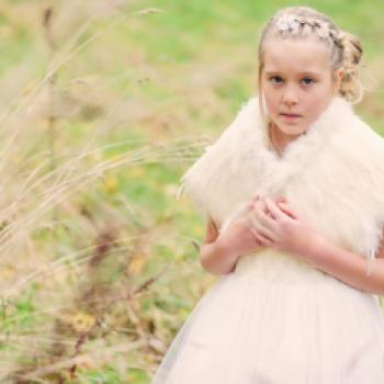 A flower girl standing in a field wearing a white flower girl dress with a tulle skirt and a feathered shawl.