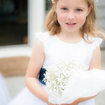 A flower girl at a wedding wearing an ivory flower girl dress with silk sleeves and a navy sash. She's holding a bouquet of flowers and wearing a floral head crown.