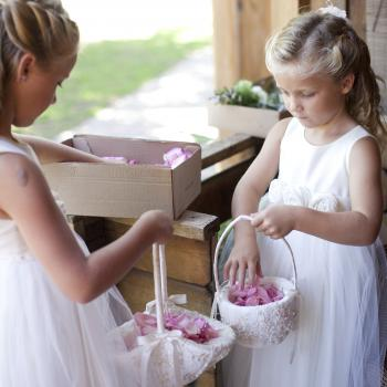 Two five year old flower girls wearing ivory dresses with blush pink roses on the sash.