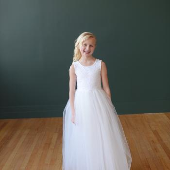 A young girl wearing a handmade, bespoke first holy communion dress in white lace with a tulle skirt.