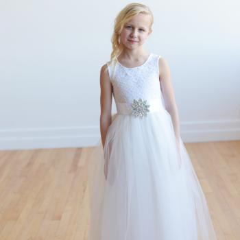 A junior bridesmaid wearing a white and ivory lace flower girl dress with a tulle skirt and a diamante applique on the sash. The dress is fully lined with satin and is also perfect as a first holy communion dress.