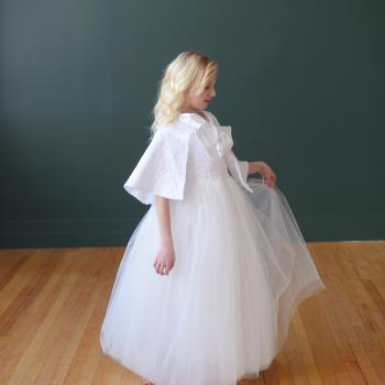 A young girl wearing a bespoke, handmade white first communion dress in lace and tulle with a flower girl cape to keep her warm!