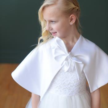A girl taking first holy communion wearing a handmade, bespoke white lace dress with a tulle skirt and a white lace cape with a big ribbon bow at the front.