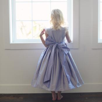 The back of a purple silk flower girl dress with a big bow and lace sleeves.