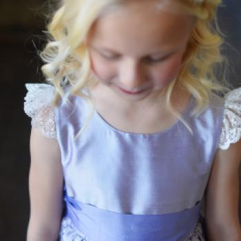 A closeup of the boice of a purple silk flower girl dress with lace sleeves.