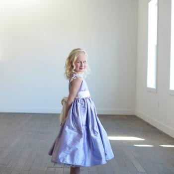 A side shot of  a flower girl wearing a purple silk flower girl dress which is tea length and has lace sleeves and a big bow.