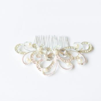 A silve and diamante bridal hair comb with delicate swirl of diamond and lines of pearls