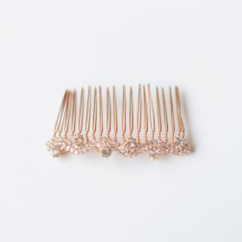 A rose gold bridal hair comb with diamante accents on a simple and delicate hair comb