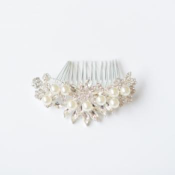 A silver bridal hair comb with swirls of diamante and pearls on a delicate hair comb.