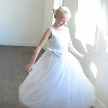 A girl taking her first communion in a white, bespoke duchess satin dress with a tulle skirt. The dress is to mid calf or ballerina length and is handmade to measure in the UK.