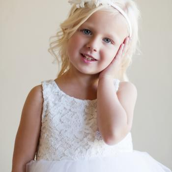A toddler flower girl and a baby wearing a lace flower girl dress with a tulle skirt in ivory and white. The bodice has a corder lace effect and is lined with satin. The tulle skirt is lined with an antistatic lining so that it's not al all itchy.