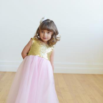 A super cute gold sequin and pink tulle flower girl dress with a pure white bel with a big bow