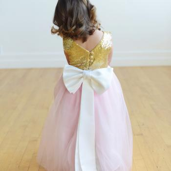 A flower girl dress with a pink tulle skirt and a gold sequin bodice. The big bow on this dress is made of white satin.