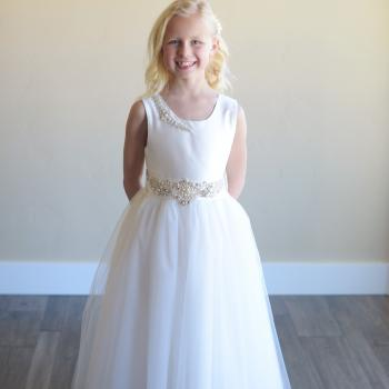 A girl in a white silk first communion dress with diamante at the waist. This is a bespoke dress which is handmade in London, UK