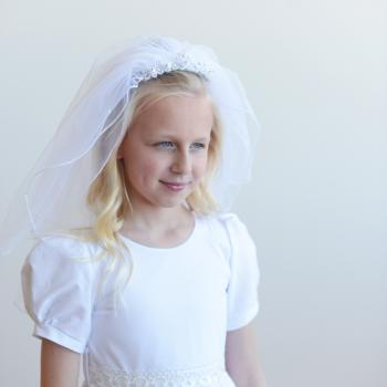 A girl wearing a double layer first communion veil with a pretty hand beaded headband