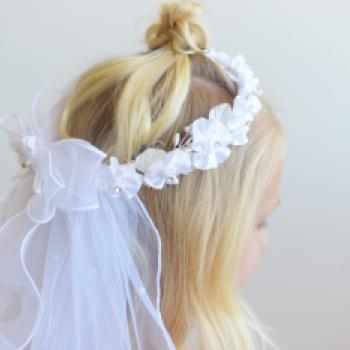 a white first communion veil with a double layer of tulle attached to a white flower crown, The veil has streamers at the back and an organza bow.