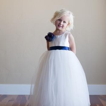 A toddler flower girl and a one year old baby wearing a white and ivory lace and tulle flower girl dress with a blue sash and white roses.