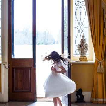 A young flower girl wearing a white flowert girl dress with a tulle skirt, lace puff sleeves and a big bow in pink.