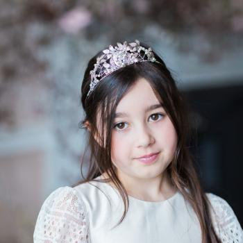 A 10 year old flower girl wearing an ivory and white flower girl dress with lace sleeves and a full lace skirt.