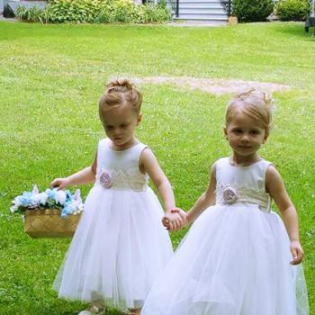 Two toddler flower girls at a wedding in the USA wearing designer, ivory flower girl dresses with a lace sash and a blush pink flower. These flower girl dresses are handmade to measure in London, UK.