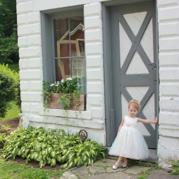 A toddler flower girl at a wedding in the USA wearing an ivory flower girl dress with a blush pink flower and a lace sash. These flower girl dresses are handmade to measure in London, UK.