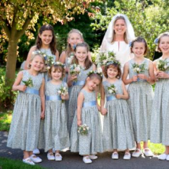 A group of young flower girls at a wedding in the UK with a bride wearing a white wedding dress. The flower girls are wearing blue floral print flower girl dresses with an ivory sash.