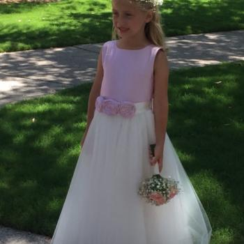 A flower girl at a wedding in Florida USA wearing a made to measure flower girl dress with a pink bodice and a full tulle skirt. The flower girl is carrying a basket of flowers with pink petals. These flower girl dresses are handmade to measure in London, UK.