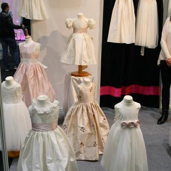 Six silk flower girl dresses on mannequins  with blush pink flowers and puff sleeves.