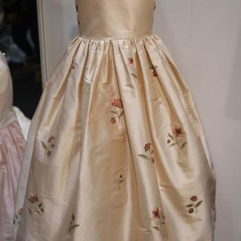 A rose pink silk flower girl dress with embroidered silk flowers and a gathered waist.