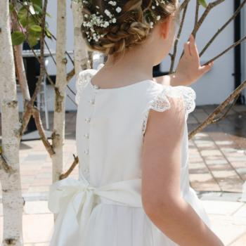 A toddler flower girl weading a toddler flower girl dress with lace sleeves and a silk bodice. The flower girl is carrying a basket of pink, peach and sherbet lemon flowers