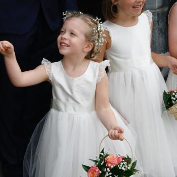 Two toddler flower girls and a baby flower girl wearing bespoke, handmade ivory flower girl dresses. The dresses have lace sleeves and a big bow belt.