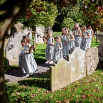 A group of flower girls walking at a church wedding wearing made to measure blue floral print dresses.