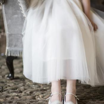 A flower girl sitting on a bench wearing white shoes and a white flower girl dress.