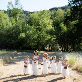 A group of flower girls and pageboys at a wedding walking and caring pink flowers. The girls are wearing ivory cotton flower girl dresses with pink roses and tulle skirts.