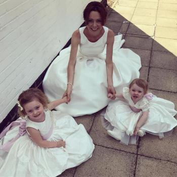 A bride and her two flower girls sitting on the floor. The bride is wearing a silk wedding dress and the flower girls wear silk flower girl dresses in ivory.